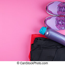 pink women's sneakers, bottle of water, clothes for sports on a pink background