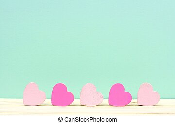 Pink wooden hearts against a turquoise background - Row of...