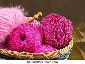 pink wool with knitting needles in basket