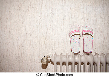 Pair of pink sandals drying on a radiator