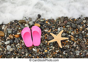 pinky slippers and starfish on pebbles near water. foam in top of image.