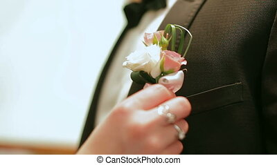 Woman pinning a boutonniere on a man