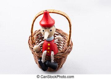 Pinochio toy figurine sitting in a basket