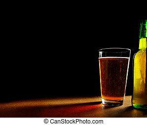 pint glass of beer and bottle, on black background