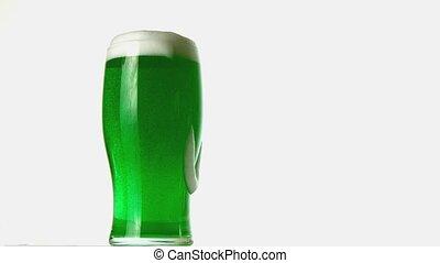 Pint of green beer overflowing in slow motion