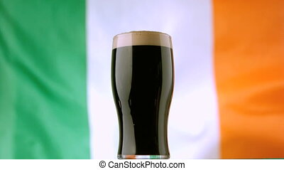 Pint of Irish stout on background of irish flag waving in...