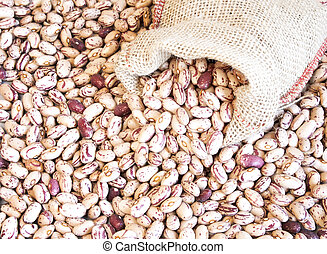 Pinto beans in small bag on pinto beans background