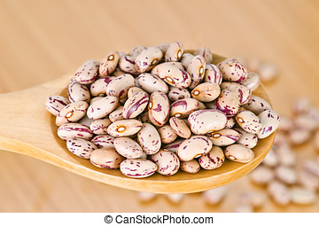 pinto beans on wooden spoon
