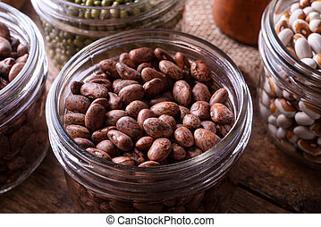Pinto Beans - Pinto beans in a glass storage container.