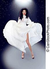 Pinup girl. Beautiful female in Blowing Dress Flying, motion shot . Merlin Monroe premier