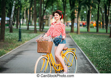 Pinup girl on retro bicycle with backet of flowers. Pin-up...