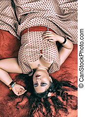 Pinup girl posing on a red bed