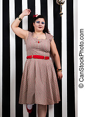 Pinup girl posing on a stripes backdrop
