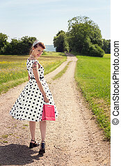 Pinup Girl with a little bag walking on a path in the nature