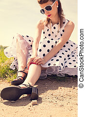 Pinup Girl with white petticoat dress waiting on the wayside
