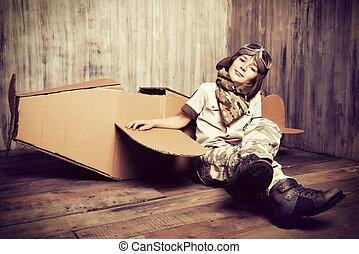 pioneer - Cute dreamer boy playing with a cardboard airplane...