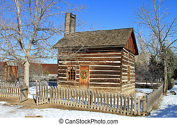 Restored 1860s log cabin, with wooden fence in the American West