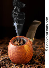 Pipe and tobacco - Wooden pipe with smoke on heap of chopped...