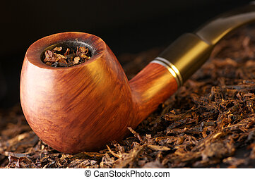Wooden pipe on heap of chopped dried tobacco leaves against black background.