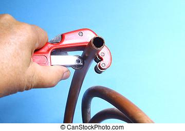 pipe cutter - hand holding a pipe cutter cutting a copper...