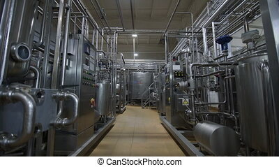 Pipeline at dairy factory. Huge cisterns for storing and...
