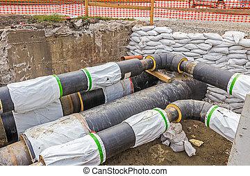 Pipeline passes under the road - White sandbag bags are full...