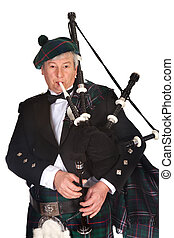 Piper playing - Scottish highlander wearing kilt and playing...