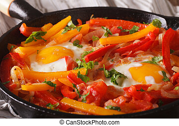 piperrada: peppers with fried eggs on the pan macro. ...