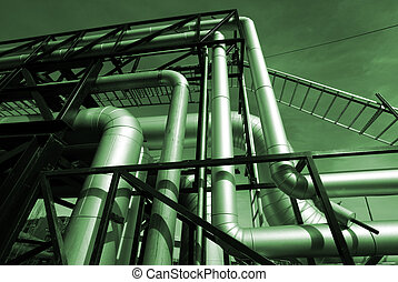 Pipes, bolts, valves against blue sky in green tones