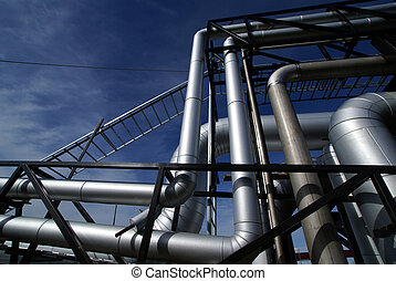 Pipes, bolts, valves against blue sky