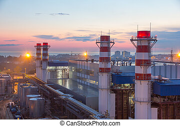 pipes of thermal power plant and and city in the evening