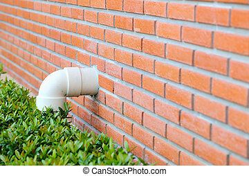 Pipes on a red brick wall