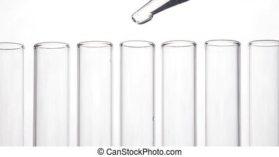 Pipette drips clean chemicals into a test tube in center of the row on white background. Chemical and medicine concept.