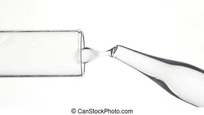 Pipette drips transparent chemicals into test tube on white...