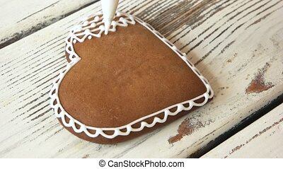 Piping a lace on fresh gingerbread cookie.