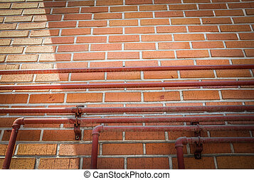 Piping on brown block wall