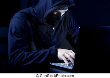 pirata informático, con, máscara, usar la computadora portátil, computadora