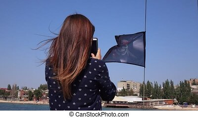 Pirate flag girl is taking pictures - Girl is taking...