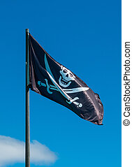 Pirate Flag - Black pirate flag flying high in the blue sky.