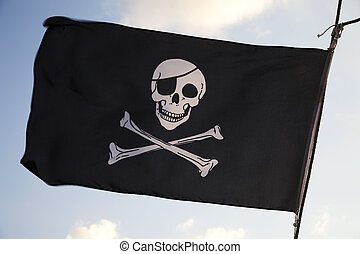 Pirate flag waving in wind against blue sky