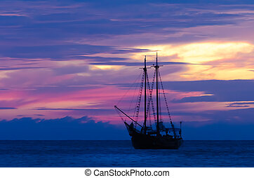 Pirate sailboat on sea navigating towards the sunset