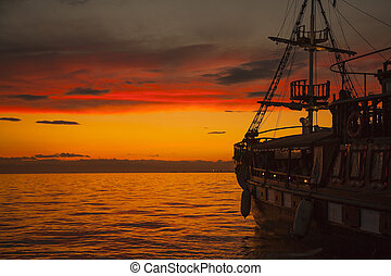 Pirate Ship - Old Fashion Sail Boat near Harbor at Sunset in...