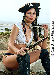 Pirate woman sitting on the beach - Beautiful pirate woman...