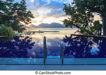 piscina, em, praia tropical, em, pôr do sol