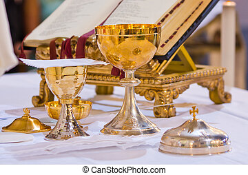 pisside and chalice contain wine and hosts on the altar of the mass