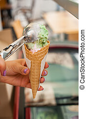 Pistachio and vanilla ice cream cone on wooden background. Girl puts a ball of ice cream in a waffle cup