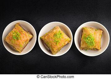 Pistachio baklava on a black plate. Dessert.