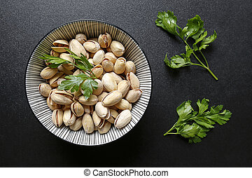 pistachio nuts in a bowl on black background