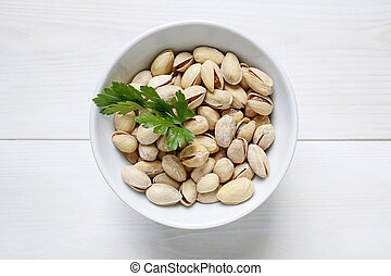 pistachio nuts in a bowl on white wooden background