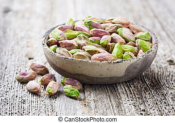 Pistachio nuts on wooden background